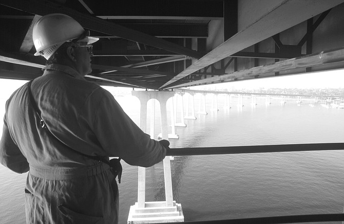 A construction worker surveying the bridge. When painters work on the outsides of the bridge, they stand on scaffolding that moves on a rail alongside it.