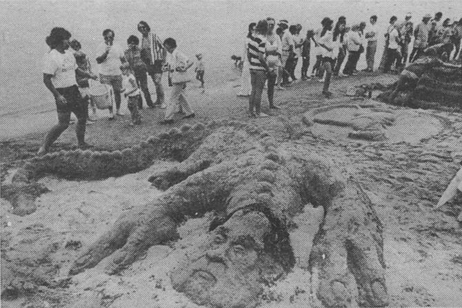 Beachgoers make a sand sculpture of former president Richard Nixon as a lizard - Image by Bob Eckert