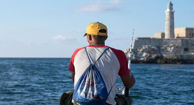 Havana fisherman on the malecón sports a SeaWorld backpack.