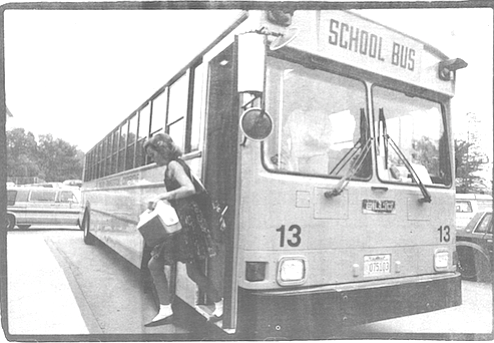 A woman with a red scarf tied over her hair hoisted what must have been a six-year-old boy onto he first step of the school bus.