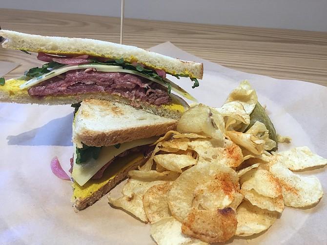 The ribeye sandwich has sliced steak, Cheddar, arugula, and pickled onion on sourdough