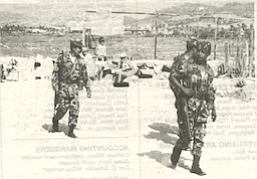 Mexican federales, soldiers in full uniform armed with rifles, patrolling the sand amongst the telescopes
