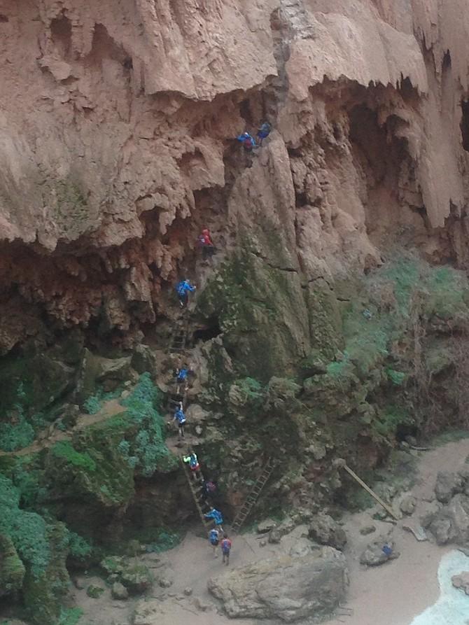 Hikers climbing the passage below Mooney Falls