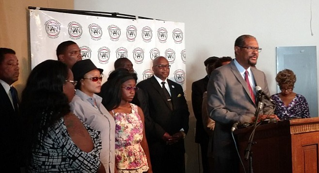 Lawyer Brian Dunn, flanked by Olango's family members and other legal counsel