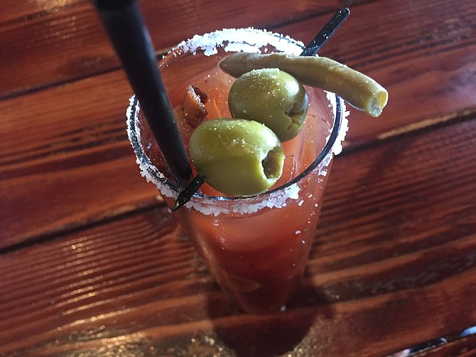 The Hills' bloody mary is spicy, tangy and comes with bacon, blue cheese-stuffed olives, and a pickled green bean.