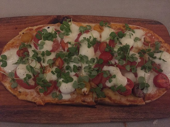 The margherita pizza has mozzarella, heirloom tomatoes and basil.