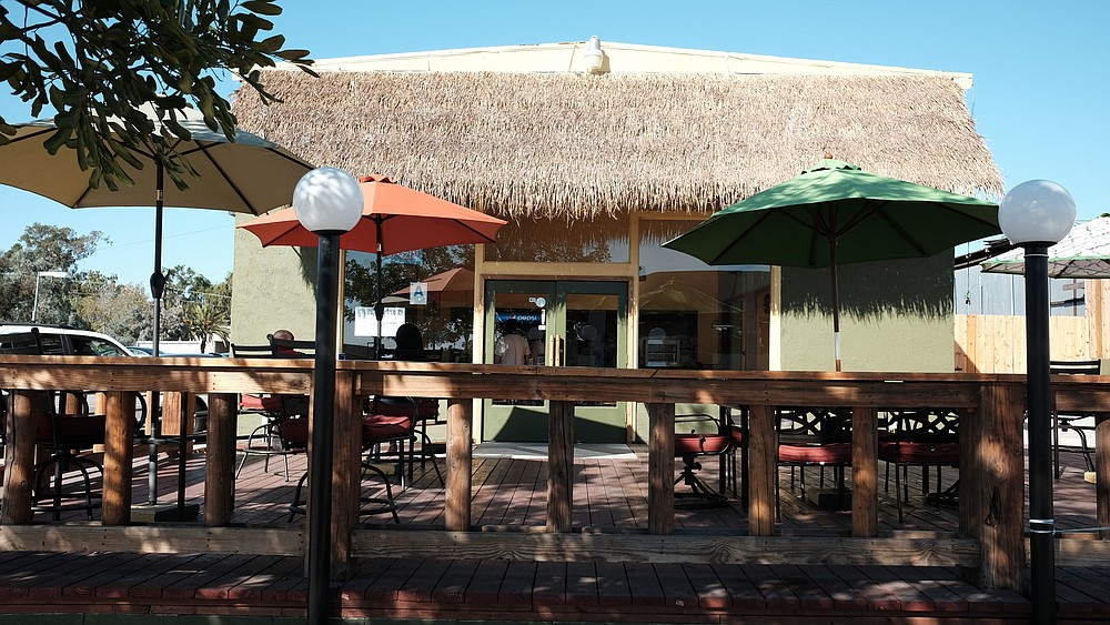 A thatched roof storefront and new deck grace Rock Steady Jamaican, formerly Island Spice Jamaican.