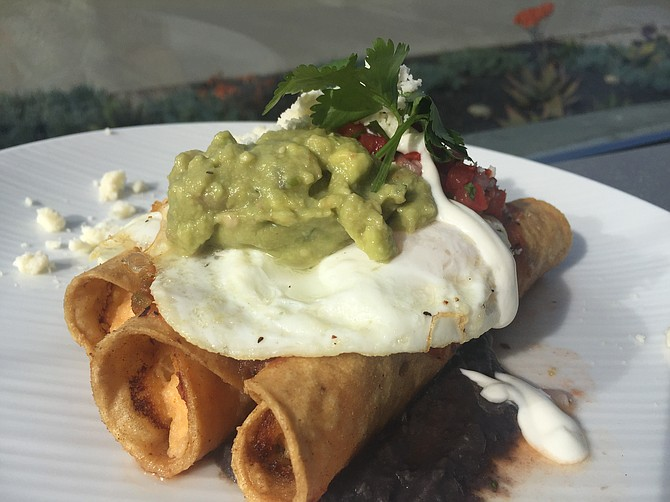 The Huevos Rancheros are served as rolled tacos filled with potatoes and come with black beans, pico de gallo, guacamole, and a lime crema.