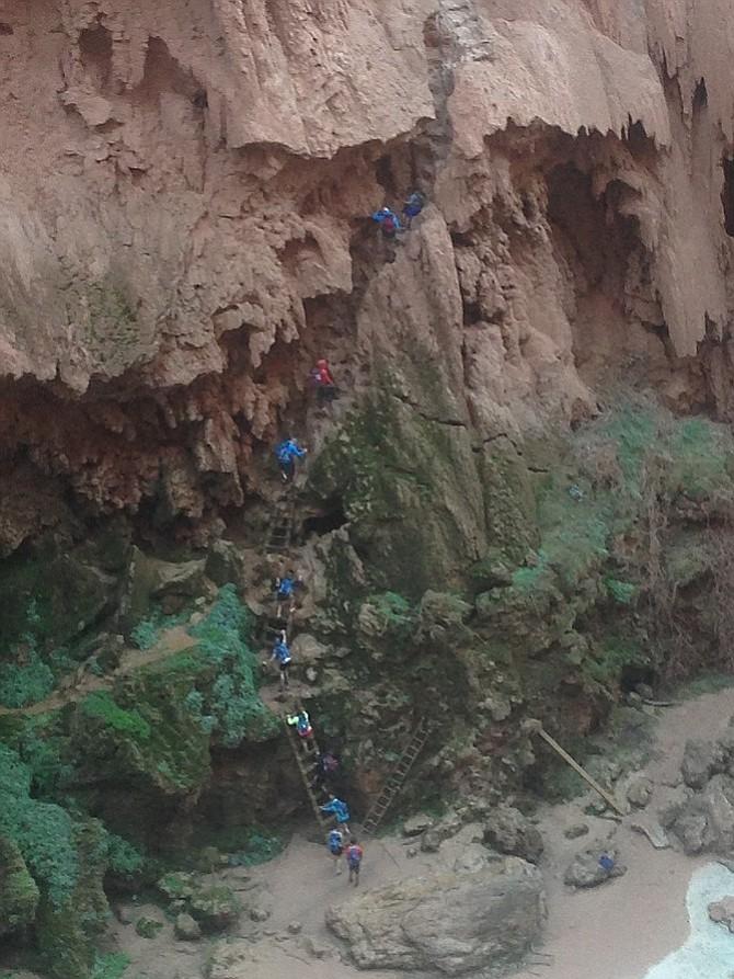 Hikers climbing the passage below Mooney Falls.