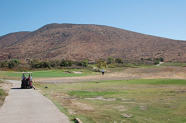"""Golfer traverses a """"forced carry"""" looking for his ball. Mt. Miguel frowns in the background."""