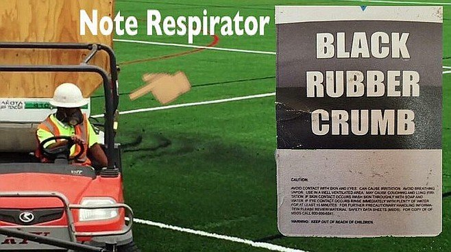 Personnel use respirator masks while spreading the rubber crumb on installed turf