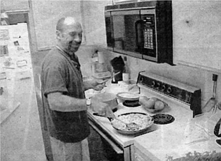 """Brian in his kitchen. """"I dipped [the chicken breasts] in egg and did the whole herb thing with bread crumbs and flour and so forth, got a crust on them, got them going."""""""
