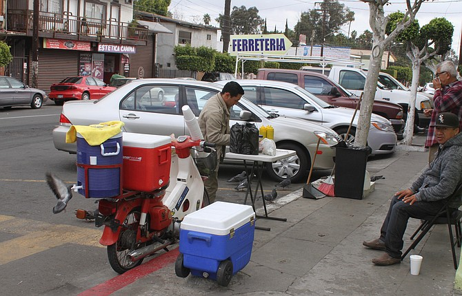 The scooter with the coolers on the corner of 4th and H is the home of Burritos la Cuarta.
