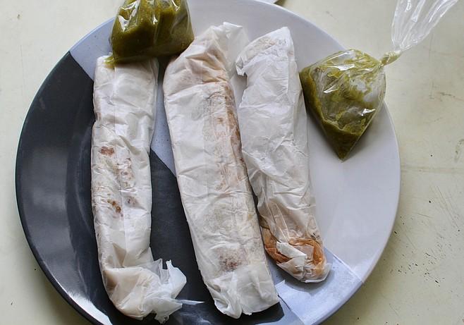 Three burritos wrapped in paper — bean and cheese, desebrada, steak and potatoes