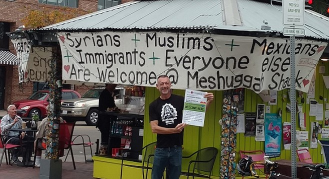 John Bertsch displays a flyer along with handmade signs at the Mission Hills Meshuggah Shack