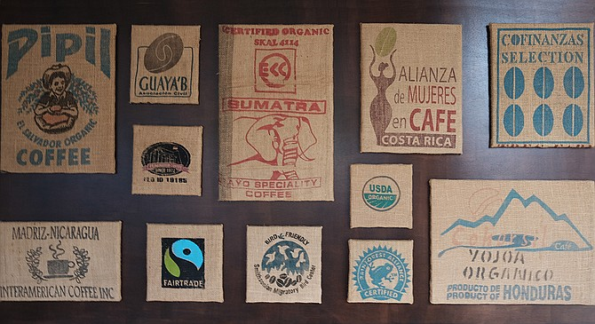 A collage of burlap coffee bags hangs in Cafe Virtuoso's updated Barrio Logan coffee shop