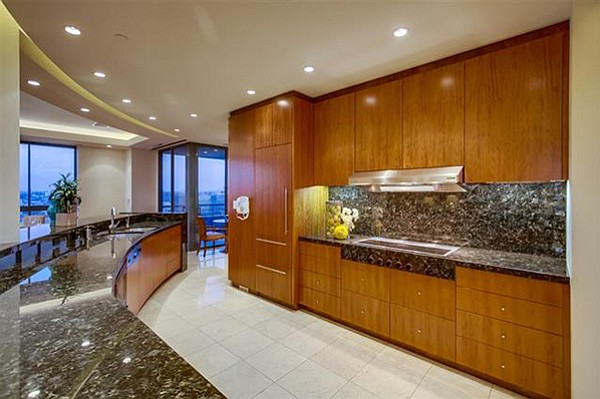 """Interior includes the """"huge kitchen"""" with a built-in wood-faced refrigerator and arched stone countertops."""