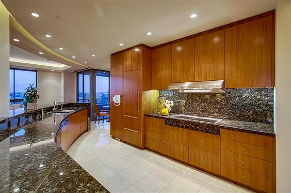 "Interior includes the ""huge kitchen"" with a built-in wood-faced refrigerator and arched stone countertops."