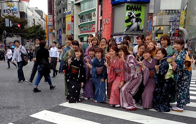 Young girls wearing kimonos and flashing v-sign in Shibuya Crossing.