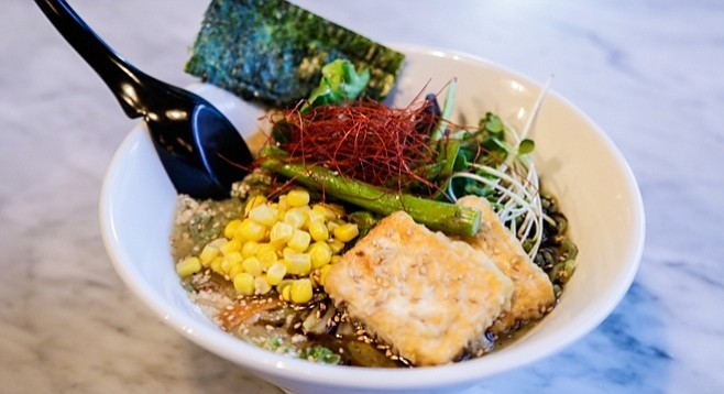 The vegan ramen comes with a variety of fresh veggies including corn, mushrooms, bean sprouts, and tofu.