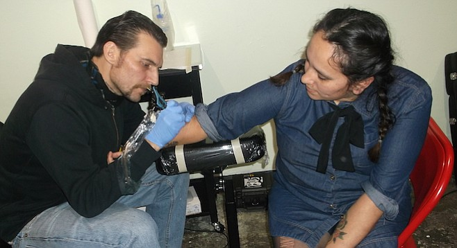 """It's kind of become a tradition for us,"" Kat said, wincing as tattoo artist Jordae worked on her right arm."