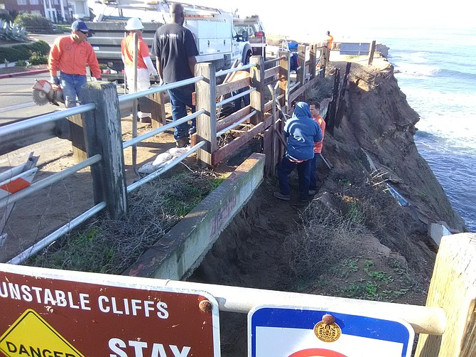 The hole opened up in the foot trail between the street guard rail and the cliff edge.