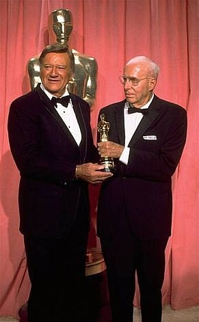 "Howard Hawks ferociously stifled any trace of pleasure while picking up the first Oscar ever, a special award for ""career achievement."" John Wayne, the presenter, demonstrated his ""personal interest"" in the award by naming the ""four movies"" he'd made with Hawks."