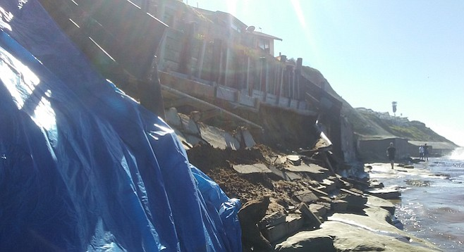 The collapsed bluff under the Pelican Point apartment complex was covered with tarps.
