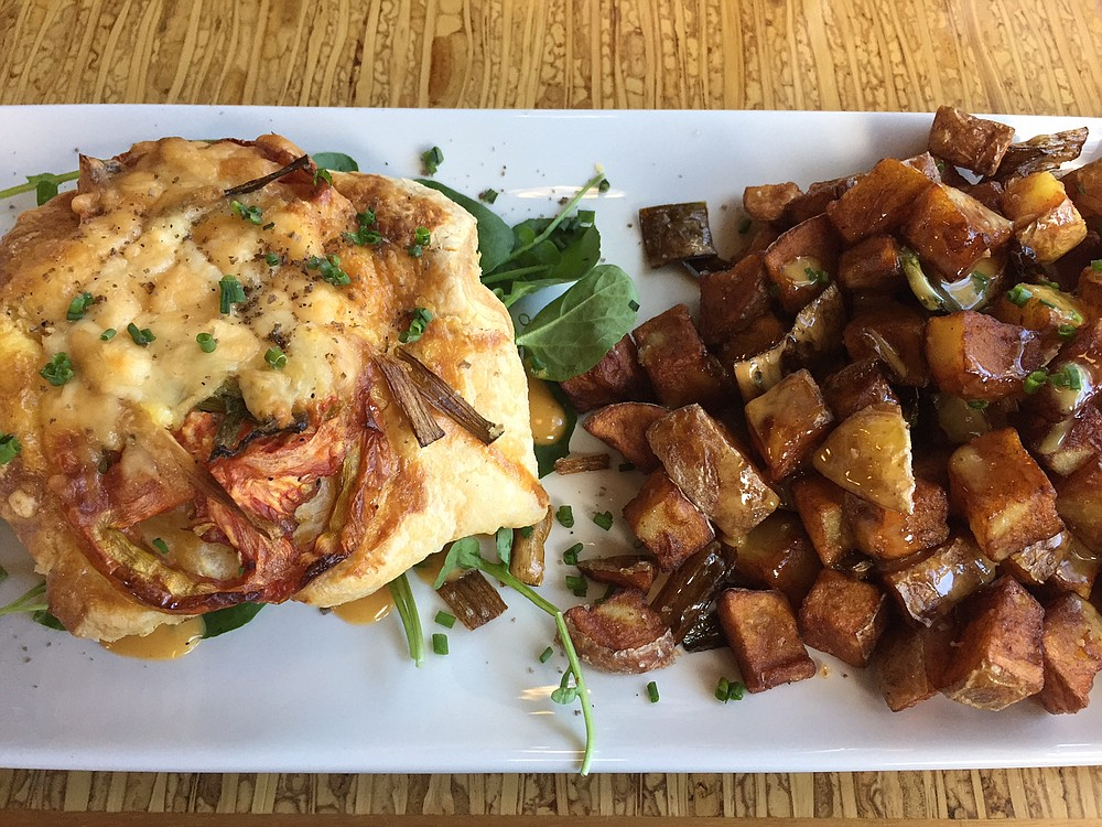 The parmesan and tomato quiche with a side of potatoes.