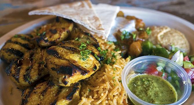 A chicken shish kebab platter, featuring shiraz salad, hummus, basmati rice, and a tomato eggplant stew.