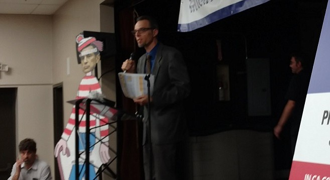 "With Issa absent, Peter Brownell and others spoke next to a cardboard cutout depicting the congressman as Waldo — as in ""where's Waldo?"""