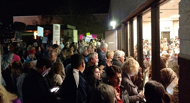 Crowded out of the meeting, many of the protesters gathered at the windows.