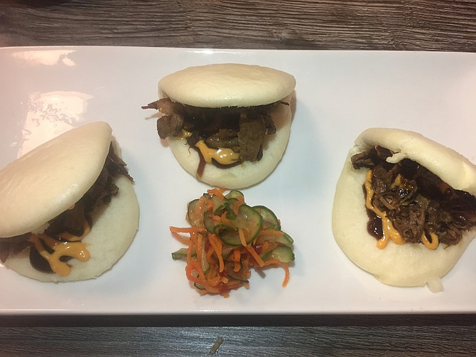 Bao Bun Tacos come with brisket and pickled vegetables with hoisin sauce.