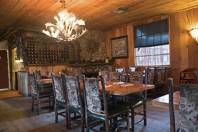 The woody dining room features a stone fireplace and deer-antler chandeliers.
