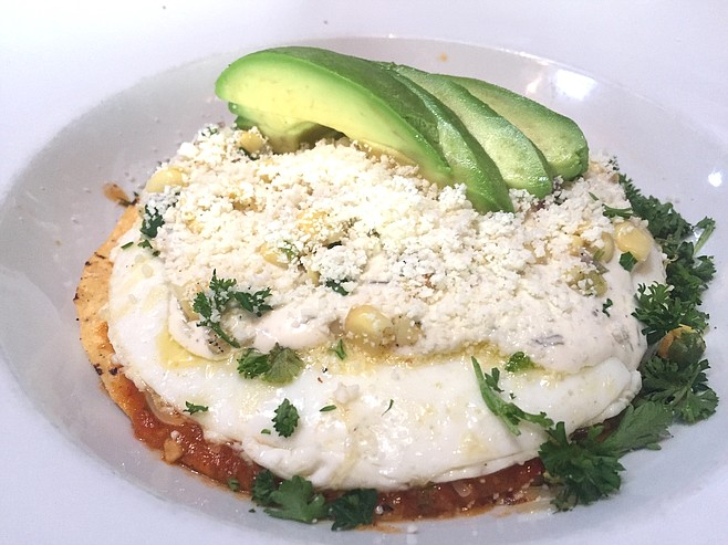 """Chilaquiles, a tostada with eggs, cheese, salsa, cotija, and corn salsa. The corn was fresh, """"really fresh."""""""