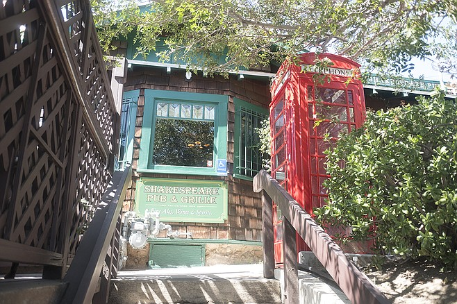 """A red vintage phone booth outside the front door screams """"London."""""""