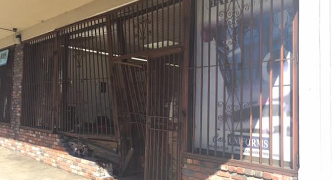 The Cal Uniforms sales manager Adrian was working only a few feet away when the car came crashing in and breaking some of the brick wall and the metal security gate.