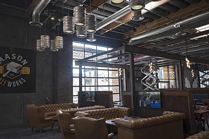 Fixtures at Urge Common House included couch seating with personal TVs, and lighting made from kegs.