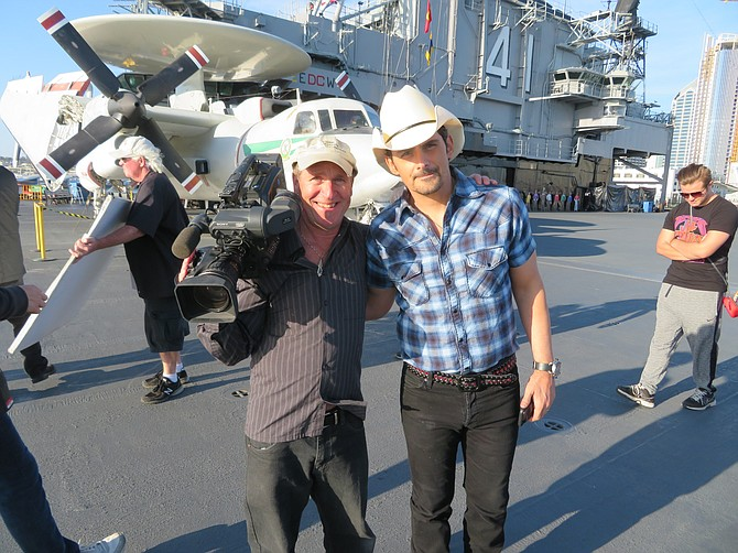 Director of Photography Mark Schulze (Crystal Pyramid Productions) and Country Music Star Brad Paisley on the flight deck of the USS Midway (Photo by Patty Mooney)