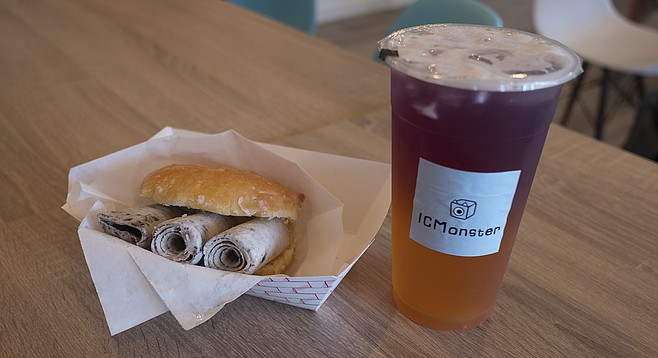 Rolled ice cream on a sandwich of glazed donut and two-tone butterfly-pea flower tea