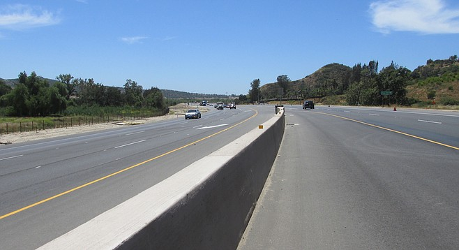 The curvy road was only 28 feet wide. The widened highway is now 88 feet wide; wider at intersections.