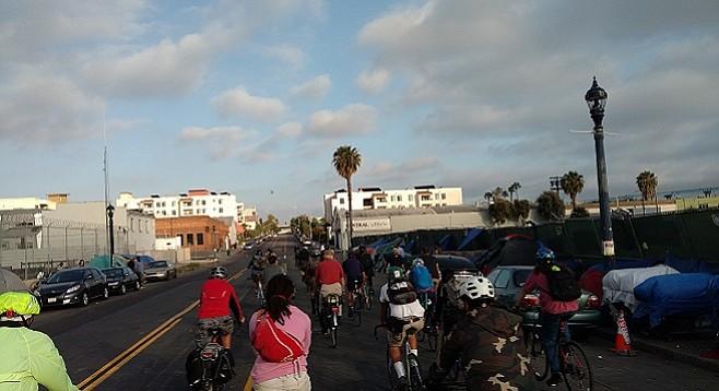 Riders pass a homeless encampment along National Avenue