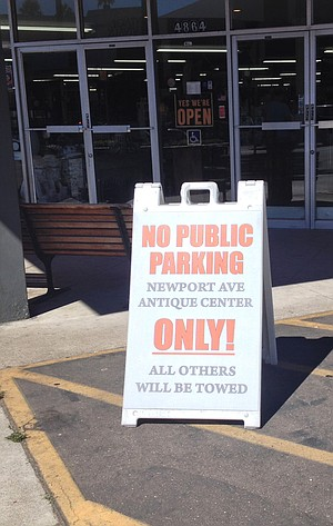 Anyone that drives onto Antique Center's lot during business hours is greeted with a sandwich board threatening to tow non-customers.