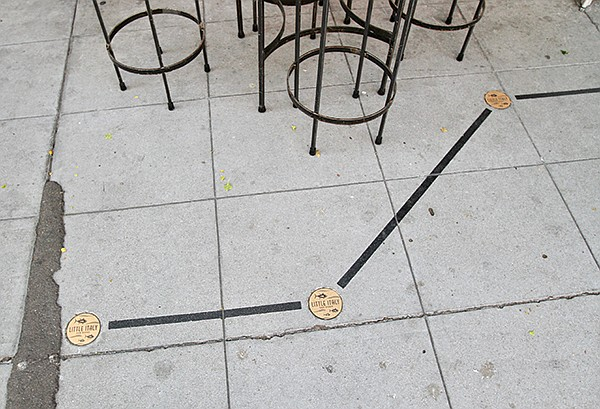 """""""Little Italy"""" brass studs have been sunk into the pavement to mark corners and black lines show the edge of the café area."""