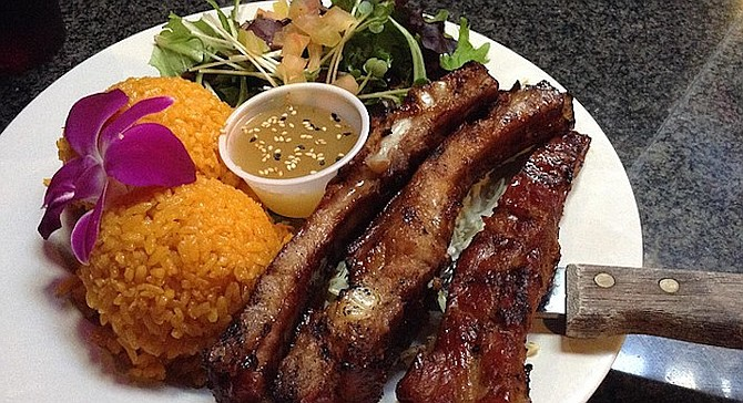 Uncle Frank's pork ribs, with achiote-stained rice and salad. The first thing you notice is the orchid.