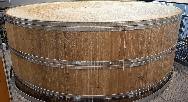 An oak foudre threatens to overflow with mashed grain fermenting for whiskey production