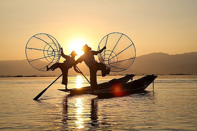 Fishermen perform a show for tourists on Lake Inle.