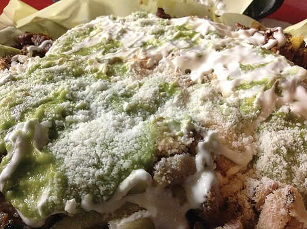 Revo fries: an ocean of guac, crema, and crumbly cheese covers a mountain of sin.