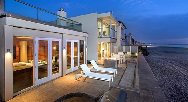 The back patio is fully tiled with a gas firepit and direct access to the public beach