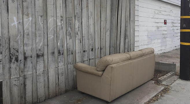 After four days, a leather couch still remains in her back alley.